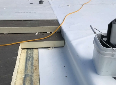Shown is a roof membrane through insulation and adhered to roof deck to prevent lateral air movement.